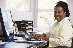 Woman in home office using computer and smiling Royalty Free Stock Photos