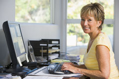 Woman in home office using computer smiling Royalty Free Stock Photo