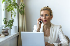Woman in the home office working on laptop and speaks on a cell phone. Stock Photos