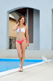 Woman at the home pool. Woman is going near the outdoor swimming pool. She is sunbathing in the yard of her house Stock Photo