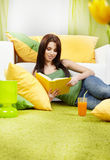 Woman at home reading a book Stock Photos