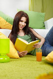 Woman at home reading a book Stock Photography