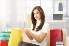 Woman at home with shopping bags. Smiling woman sitting at home with shopping bags, checking purchased goods, looking at camera Royalty Free Stock Images