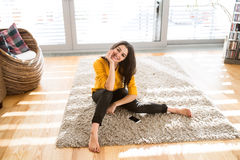 Woman at home sitting on carpet, smartphone next to her Royalty Free Stock Image