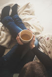 Woman at home sitting in comfy armchair and drinking tea, view from above. Young woman at home sitting in comfy armchair and drinking tea, view from above Royalty Free Stock Photo