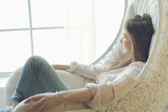 Woman at home sitting on modern chair in front of window relaxing in her living room.  Stock Photography