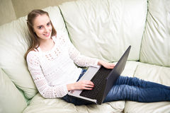 Woman at home sitting on sofa and using her laptop computer Royalty Free Stock Image