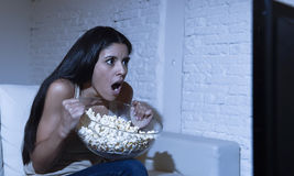 Woman at home sofa couch in living room watching television scary horror movie or suspense thriller Stock Image