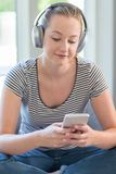 Woman At Home Streams Music From Mobile Phone To Wireless Headph Royalty Free Stock Images