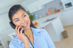 Woman at home talking on land line telephone. Land stock photo