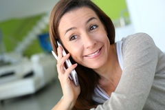 Woman at home talking on phone with an happy look Stock Photos