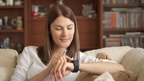 Woman at home texting on smart watch. Beautiful young female professional working on smartwatch stock footage