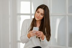 Woman at home using smartphone. Beautiful woman at home in living room, using her smartphone, smiling Royalty Free Stock Image
