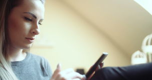 Woman at home using smartphone. Footage of a woman at home using smartphone. Woman texting stock video footage