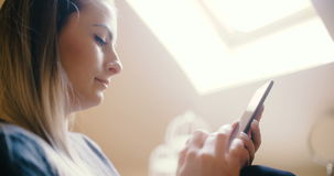 Woman at home using smartphone. Footage of a woman at home using smartphone. Woman texting stock footage