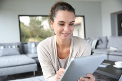 Woman at home using tablet Stock Image