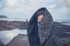 Woman with hood on beach Stock Photo