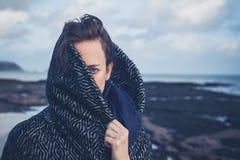 Woman with hood on beach Stock Photos