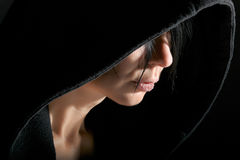Woman in hood in dark. Woman portrait in low key with contour from hood Stock Photography