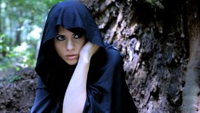 Woman with hood hiding in forest stock video footage