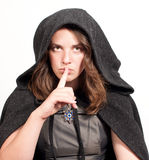 Woman in hood puts forefinger to lips Royalty Free Stock Photos
