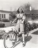Woman in hooded coat riding bicycle Royalty Free Stock Photos