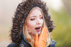Woman in hooded jacket yawning. Stock Photo