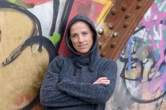 Woman in a hoodie leaning against graffiti Stock Image