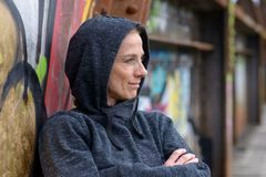 Woman in a hoodie leaning against graffiti Royalty Free Stock Image