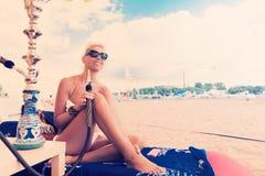 Woman with hookah on the beach in bikini Stock Image