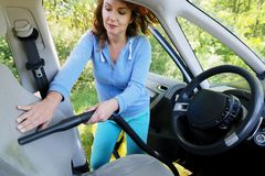 Woman hoovering a seat in car Royalty Free Stock Photos