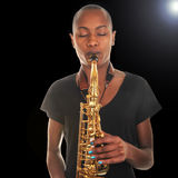 Woman with a horn. Nice Image on Black Of a Musician playing a saxaphone Stock Photos
