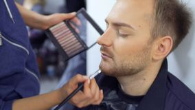 Makeup artist paints beard of the man. Woman with horrible greasepaint on face helps her colleague and makes a greasepaint on his face with brush. Woman paints stock footage