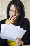 Woman horrified by bills Royalty Free Stock Images