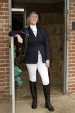 Woman hors rider standing at a stable door. Smartly dressed horse rider standing at a stable door wearing dark blue riding jacket, jodphurs and boots. November Stock Photography