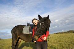 A woman and a horse. Woman and a horse standing in a field on the background of the cloudy sky Stock Photo