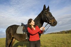 Woman and a horse. Woman and a horse standing in a field on the background of the cloudy sky Royalty Free Stock Photo