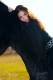 Woman and horse. Young beutiful woman leaned on black horse stock photos