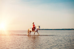 Woman and horse on the background of sky and water. Girl model o Stock Photo