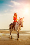 Woman and horse on the background of sky and water. Girl model o Royalty Free Stock Images