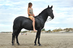 Woman and  horse on the beach. Beautiful black horse on the beach and beautiful woman Royalty Free Stock Image