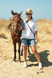 Woman with horse on the beach. Woman holding brown horse on the beach Stock Photo