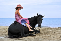 Woman and  horse on the beach Stock Photo