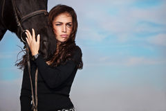 Woman and horse. Beautiful brunette woman and black horse, outdoor royalty free stock photo