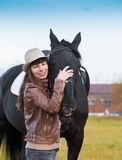 Woman and  horse, beige pullover, leather jacket, jeans, hat, cl Stock Photo
