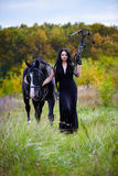 Woman with horse and crossbow in the forest Stock Photo