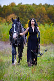 Woman with horse and crossbow in the forest Royalty Free Stock Images