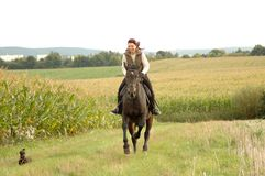 Woman, horse and a dog. Woman riding a horse and a dog compete Royalty Free Stock Image