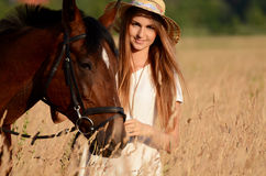 The woman on a horse in the field Stock Photography