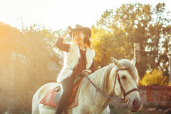Woman on horse in hat. Beautiful elegance woman cowgirl, riding a horse. brown leather jacket and hat. Has slim sport body. Portrait nature. People and animals Stock Photo